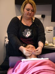 Jennifer Garlock gives a customer a facial massage during a session at Sweet Cheeks Skin Spa in the Sutton Center in Port Clinton.