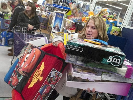 Kerry Neiderer of Hanover has her hands and chin full of toys as she waits on line at Toys R' Us in West Manchester Township during Black Friday 2011. DAILY RECORD/SUNDAY NEWS--JASON PLOTKIN
