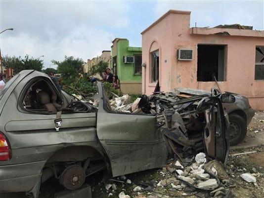 Un grupo de personas se para cerca de un vehículo destruido después que un poderoso tornado pasó por Ciudad Acuña, en el norte de México, el lunes 25 de mayo de 2015. Un tornado tocó tierra el lunes en la ciudad mexicana ubicada en la frontera con Estados Unidos, donde destruyó casas y volcó autos. Al menos 13 personas murieron, de acuerdo con las autoridades. El tornado barrió una zona de siete manzanas. (Foto AP)