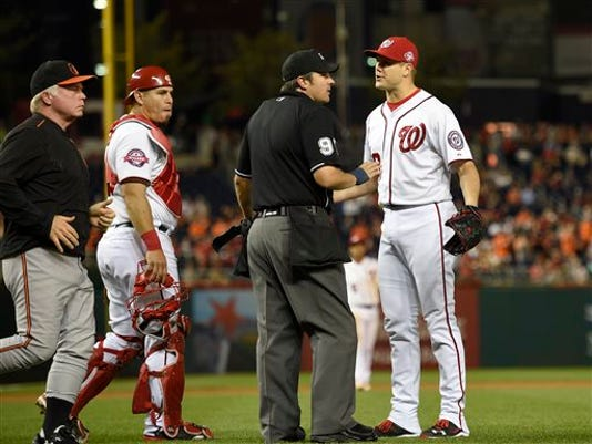 Washington Nationals relief pitcher Jonathan Papelbon, right, argues with umpire Mark Ripperger, second from right, during the ninth inning of an interleague game as Baltimore Orioles manager Buck Showalter, left, walks on the field, Wednesday, in Washington. Papelbon was ejected for hitting Baltimore's Manny Machado with a pitch. Washington Nationals catcher Wilson Ramos, third from right, looks on. The Orioles won 4-3.