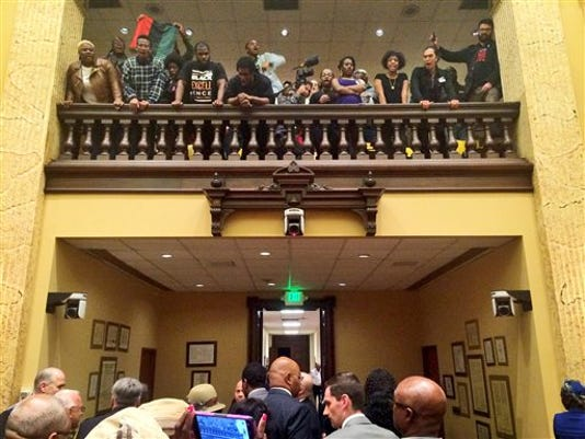 Protesters shout as council members leave the chamber at city hall in Baltimore, Wednesday, Oct. 14, 2015. A city council subcommittee voted to make Kevin Davis the permanent police commissioner Wednesday.