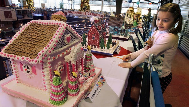 """Lindsay Crivello casts her people's choice ballot for the """"Hello Kitty"""" gingerbread house on display at the Milwaukee Public Market in 2013."""