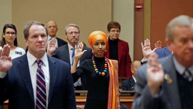 State Rep. Ilhan Omar, center, takes the oath of office as the 2017 Legislature convened Tuesday, Jan. 3, 2017, in St. Paul, Minn. Omar is the nation's first Somali-American to be elected to a state legislature in the U.S. (AP Photo/Jim Mone)