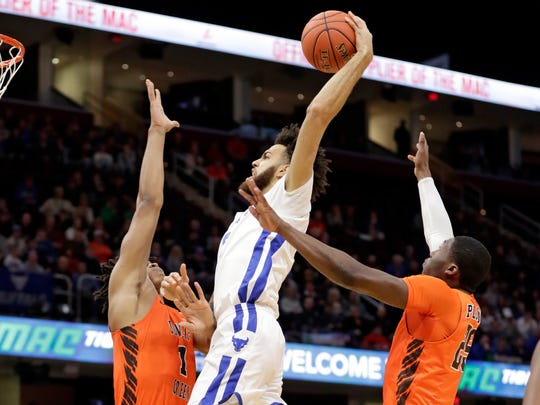 Buffalo's Jeremy Harris, center, drives to the basket against Bowling Green's Demajeo Wiggins, left, and Daeqwon Plowden during the first half of an NCAA college basketball championship game of the Mid-American Conference men's tournament, Saturday, March 16, 2019, in Cleveland. (AP Photo/Tony Dejak)