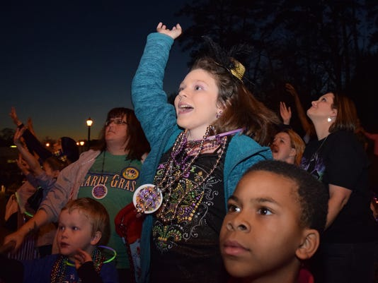 """Madison Boyer (center) excitedly yells for beads as she and her brother Nathan Boyer (left) and Hykeem Mix attend  """"Light the Night"""" Mardi Gras parade held Friday evening. """"Light the Night"""" crosses from Pineville into Alexandria and is Central Louisiana's only nighttime Mardi Gras parade."""