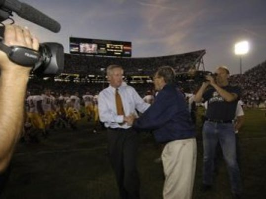 Former Minnesota coach Glen Mason, a Colonia native who has worked for the Big Ten Network since 2007, shakes hands with late former Penn State coach Joe Paterno after a game between their teams. (File photo)
