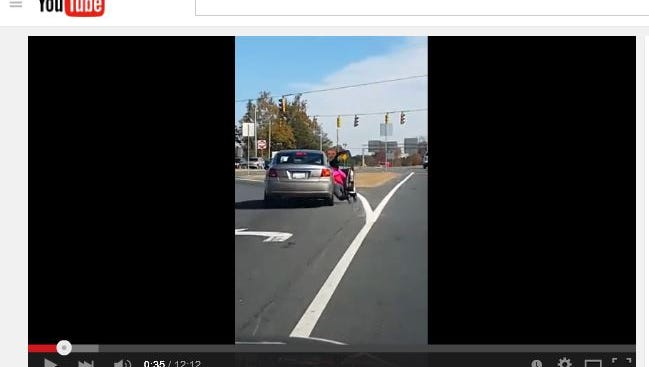 A screenshot of the video shows the woman in a bright pink jacket being dragged alongside the car.