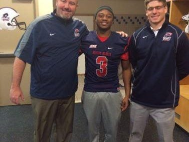 Robert Morris assistant head coach Scott Farison, left, Delano Madison and receivers coach Nick McVay smile in the locker room. Madison's Michigan Elite 7-on-7 coach George Yarberry helped him meet with Farison.