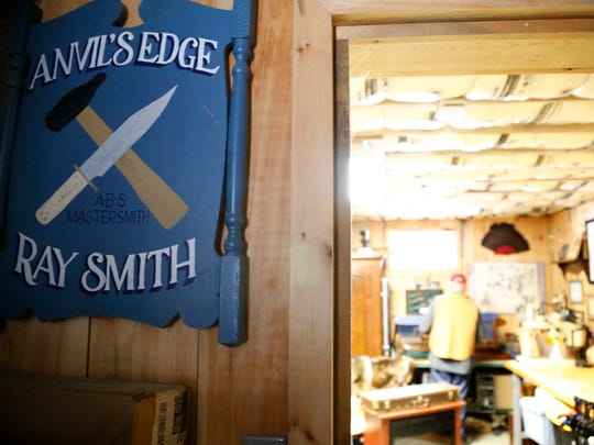 Anvil's Edge owner Ray Smith rummages through his basement workshop in his Erin home Feb. 3. When he first began his blacksmith and bladesmith endeavors in the 1980s, Smith would welcome customers with the blue sign.