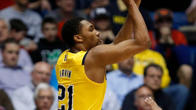 Michigan guard Zak Irvin (21) shoots while guarded by Tulsa guard James Woodard (10) during the first half of U-M's win Wednesday in Dayton, Ohio.
