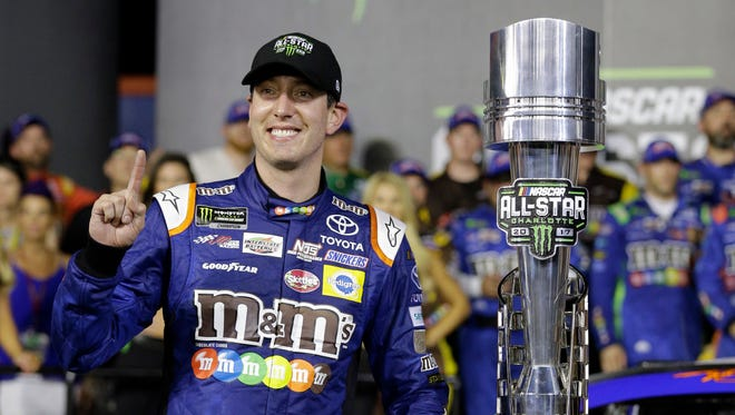 Kyle Busch poses with the trophy in Victory Lane after winning the NASCAR Cup series All-Star race on Saturday.