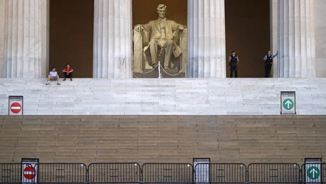 """Visitors and members of the U.S. Park Police rest at the Lincoln Memorial as sunrise nears in Washington, D.C., the morning after massive protests over the death of George Floyd. A manipulated photo circulating online depicts the statue of Abraham Lincoln covered in graffiti and """"BLACK + BROWN LIVES MATTER"""" written on the wall. The Lincoln statue and surrounding monument were not vandalized during recent protests, according to a spokesman for the National Mall and Memorial Parks, although some graffiti was left at the steps leading up to the monument."""