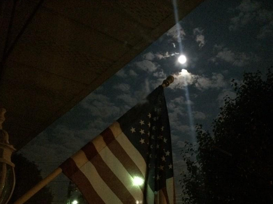 Sunday night Supermoon shines brightly with an American flag in the forefront.