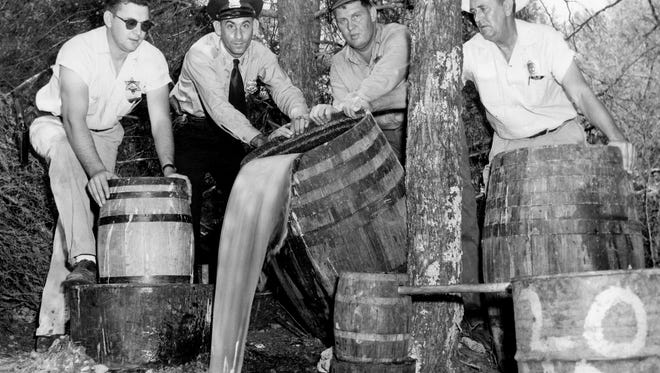 Rutherford County Deputy Sheriff Dudley Comer, left, Murfreesboro police Patrolman Henry Carlton, Deputy Lester Singleton and Sheriff W.H. Wilson pour out mash seized in a raid on two moonshine stills near Murfreesboro on Aug. 29, 1957. Raids took place in Williamson County as well as surrounding counties.