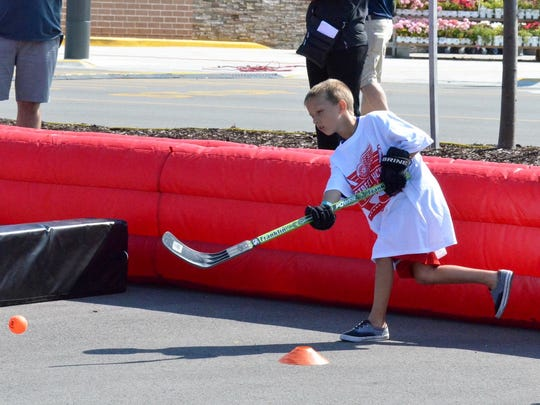 Lake Ann native Barrett Schook shoots during the Detroit Red Wings Summer Street Hockey Tour hosted Monday, July 18, 2016 at Meijer in Acme, MI.