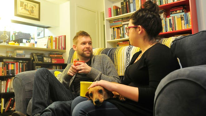 With their dog, Conner, Sam Harper and his wife, Ashley, talk in their living room. Sam Harper, 29, was diagnosed with Lou Gehrig's disease in August.