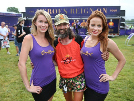 NASCAR fan John Stewart of Indianapolis with the Crown Royal girls McKenzie Carney of Indianapolis and Margo Andrews of Valparaiso at the Indianapolis Motor Speedway before the Brickyard 400 on Sunday, July 27, 2014.