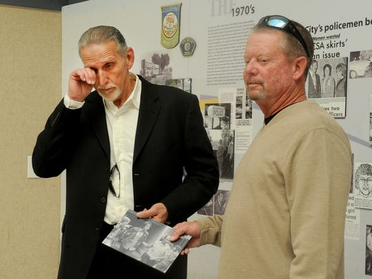 Rick Freeman, right, a former Simi Valley Police Department officer, helps Craig Coley take down a picture that showed his arrest in 1978. Coley, who was wrongfully convicted of a double murder, was pardoned and released from prison. The photo of him being arrested had hung inside the Simi Valley police station as part of a display of the department's history.