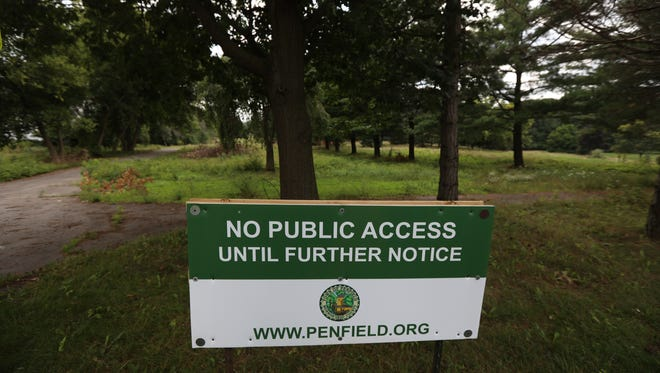 Signs posted on Clark and Whalen roads in Penfield warn people to stay off the former Shadow Pines golf course until town workers can clear debris and downed trees.