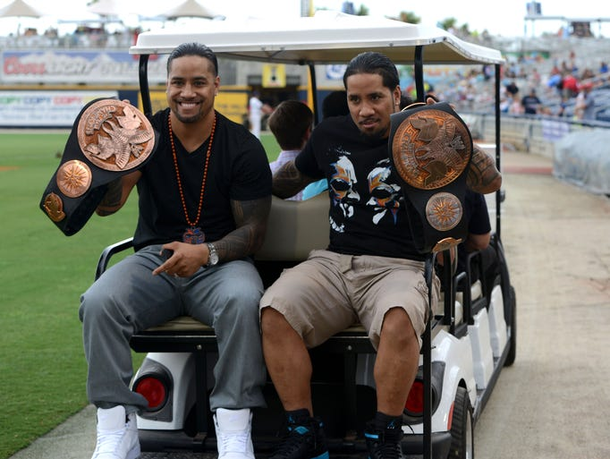 Professional wrestlers and World Wrestling Entertainment, Inc. tag-team champions  Jimmy and Jey Uso show off their belts while taking a spin around Blue Wahoo stadium on Thursday night before throwing out a first ceremonial pitch.