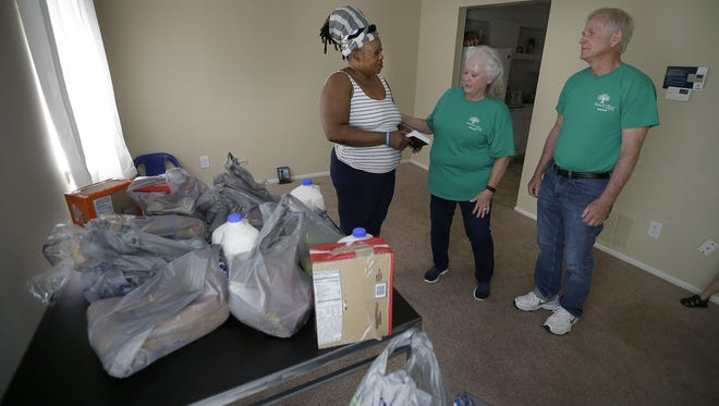 Heaven's Cupboard is a food ministry operated by Mount Olive Ministries  in Wayne Township. They get referrals from schools and buy a week's worth of groceries for families in need. Here, volunteers Brenda and Leonard Stringer deliver groceries to Omowunmi Olayinka at her apartment near Ben Davis High School.