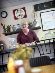 Owner Denise Fisher is behind the counter of her cafe,