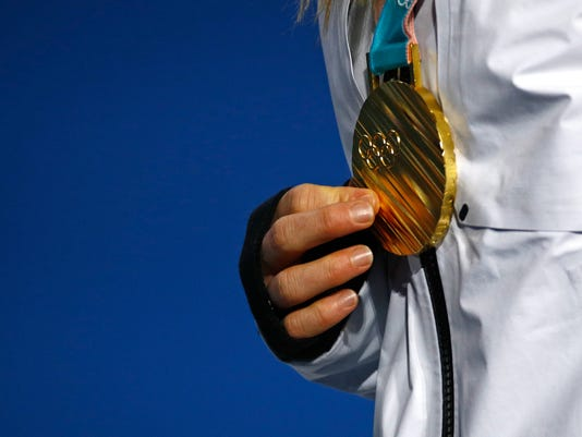 Women's slopestyle gold medalist Jamie Anderson, of the United States, holds her medal during a medal ceremony at the 2018 Winter Olympics in Pyeongchang, South Korea, Monday, Feb. 12, 2018. (AP Photo/Patrick Semansky)