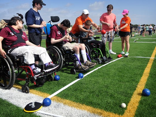 Volunteers assist Special Olympians in the bocce ball competition during Thursday's Special Olympics Unified Sports Day at Rider High School.