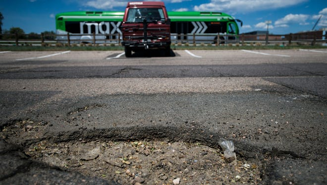 A MAX Transit bus heads North past the pothole-laden parking lot used primarily by people riding the bus on Tuesday, June 5, 2018, at the old Kmart parking lot at East Drake Road and South College Avenue in Fort Collins, Colo.