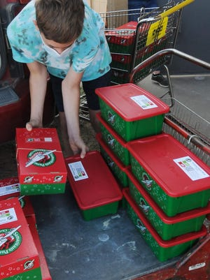 Volunteer Linkin Smith, 11, unloads the Operation Christmas Child boxes from a vehi-cle outside of the CrossRoads Church, 1125 W. South Street in Salina, on Friday af-ternoon. Samaritan's Purse is collecting shoebox gifts to give to children in need around the world. The CrossRoads Church and The First Southern Baptist Church, 2401 S. Ohio Street, in Salina will be offering a curbside drop-off for the boxes until Monday, Nov. 23.