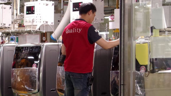 A quality control worker checks LG washing machines before they are packaged.