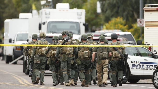A SWAT team walks down South Longmore Road near Adams Elementary School searching for a gunman on Wednesday, Mar. 18, 2015.