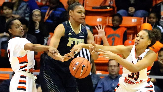 FIU's Brianna Wright, center, is harassed by UTEP's Starr Breedlove, left, and Daeshianna McCants, right, Thursday night in the Don Haskins Center. The Miners prevailed, 70-52.