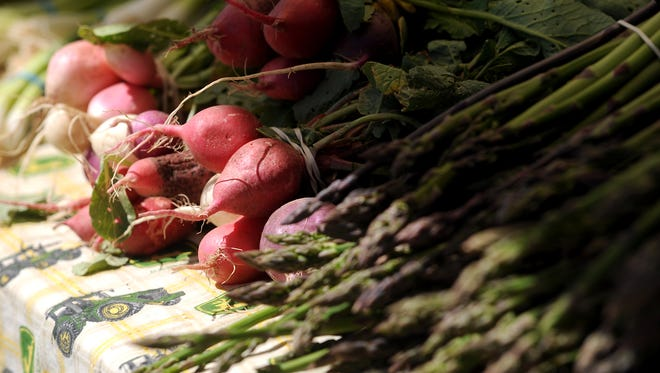 Radishes and asparagus are laid out on a table at the Millers Farms booth on Sunday, June 6, at the farmers market located in the parking lot on the southwest corner of Harmony and Lemay in Fort Collins.