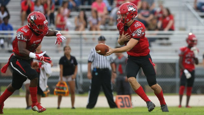 North Fort Myers High School quarterback Toby Noland hands off during a game against Riverdale earlier this season.