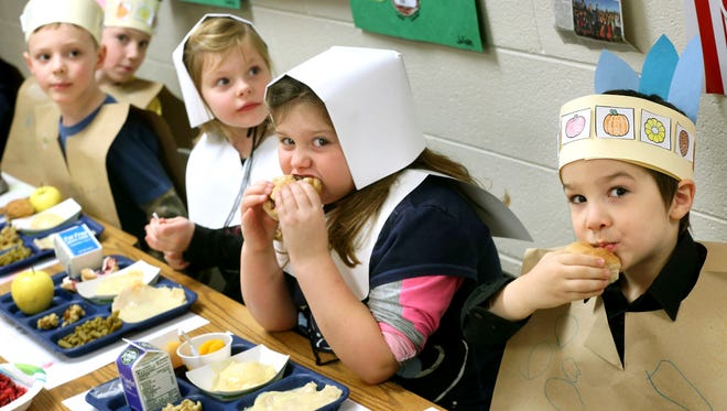 Wearing the Indian and Pilgrim costumes they fashioned to recreate the first Thanksgiving, kindergarten students at Virginia Avenue Charlotte DeHart Elementary School in Winchester, Va. enjoy a Thanksgiving meal with all the trimmings for lunch on Nov. 20.