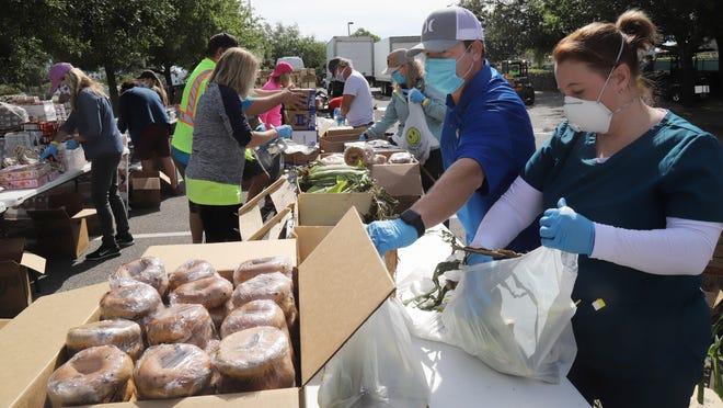 Volunteers sort and bag food Saturday during Destin Harvest's drive-thru food giveaway at Morgan Sports Complex.