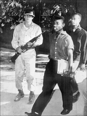 Black students are escorted by U.S. paratroopers as they leave Little Rock Central High School on Sept. 25, 1957.