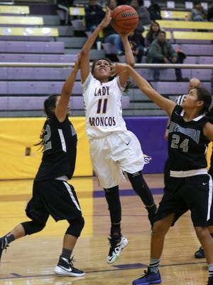 Kirtland Central's Deiondra Smith attempts a shot over Miyamura's Lauryn Thomas (24) and Michelle Toadlena (22) on Tuesday at Bronco Arena in Kirtland.