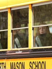 A Hawkins Middle School student looks out the window as students wait to leave buses to be reunited with their parents Wednesday at the Theler Center.