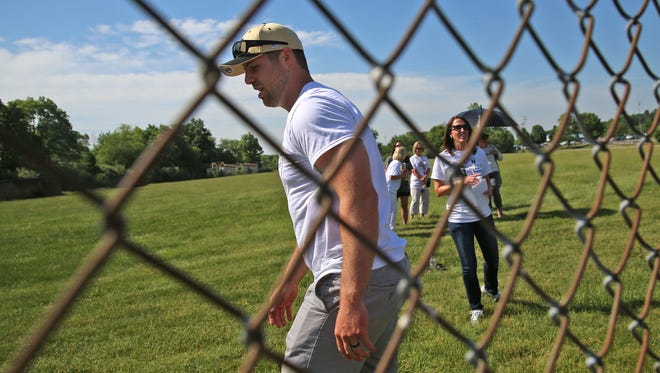Noblesville West Middle School science teacher Jason Seaman walks back to his seat after talking to his students, over a fence, at the IHSAA baseball championships, the Noblesville vs Hamilton Southeastern game, Monday, May 28, 2018.  This is the first time his students have seen him since Friday May 25's school shooting.  When a student opened fire in the seventh grade science classroom, Seaman intervened to stop the shooter from shooting more students.  He and one student were shot in the incident.  He was shot three times.  He told the students he couldn't hug them just yet, because he was still a little tender, but he could high five them.
