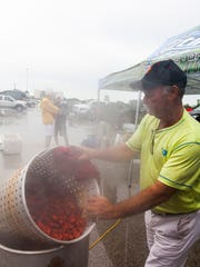 Die-hard fan Ronnie Gilmore boils crawfish in the wet parking lot at The Tigue as inclement weather delayed play Saturday.
