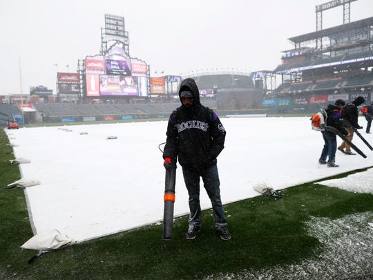 Grounds crew members use blowers to clear a light snow as it falls over Coors Field before the Colorado Rockies host the Atlanta Braves in a baseball game Friday, April 6, 2018, in Denver. (AP Photo/David Zalubowski)