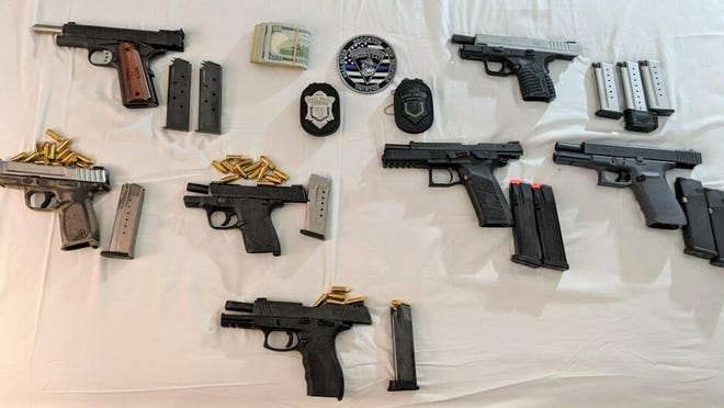 """During a traffic stop resulting from a violation of the """"hands-free"""" driving law in Raynham Tuesday evening, Massachusetts State Police troopers busted an illegal operation to sell guns and ammunition transported from Florida."""