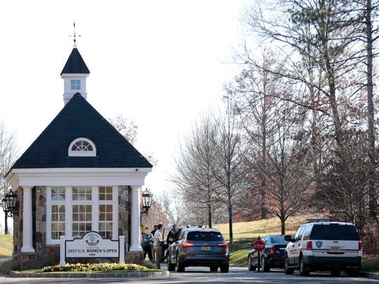 Officials gather at the entrance of Trump National Golf Club, Friday, Nov. 18, 2016, in Bedminster, N.J. President-elect Donald Trump arrived at the club late Friday afternoon.