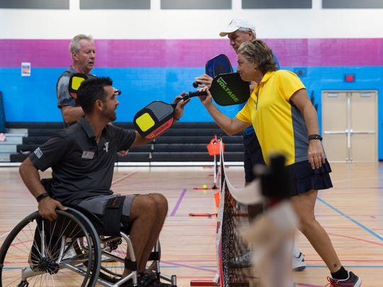 Dayan Solar, front left, and Mindy Rashbaum, front right, along with their teammates, congratulate each other after a hard fought game of pickleball at the Greater Naples YMCA, Tuesday, Jan. 10, 2017 in Naples. A newly-created Adaptive Sports Program, created by Rashbaum, has  given Solar, who is diagnosed with multiple sclerosis, as well as many other wheelchair bound athletes a competitive outlet to play pickleball at a high level.