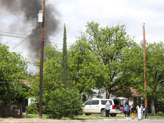 Residents stand on the street while emergency crews fight a blaze in the 700 block of Spaulding Street on Friday, April 14.