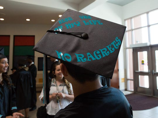 "Austin Diaz, 18, a graduating senior from Oñate High School, chats with friends before walking the halls of Sonoma Elementary school, Thursday, May 18, 2017. The ""No Ragrets"" wording on his cap is in homage to a scene from the movie, ""We're The Millers."""