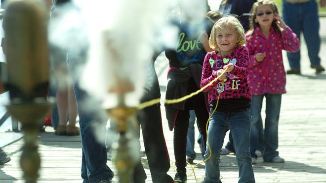 Kylie Meyers, of St. Clair, pulls a string to sound a steam whistle during Whistles on the Water event in Palmer Park.