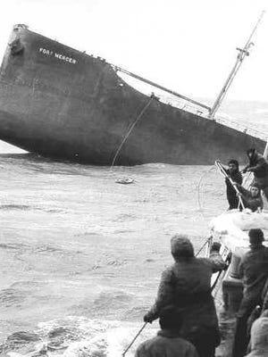Crewmen of the U.S. Yakutat pull in a rubber liferaft with the last two survivors from the bow section of the broken tanker SS Fort Mercer.